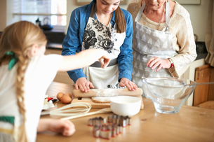 Senior woman and granddaughters rolling dough for Christmas tree cookiesの写真素材 [FYI03568805]