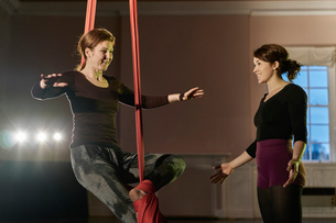 Two young female aerial acrobats practicing balance on silk ropeの写真素材 [FYI03568827]