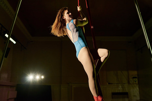 Waist down view of young female aerial acrobat climbing silk ropeの写真素材 [FYI03568834]