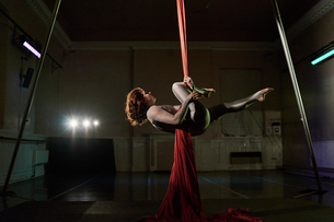Young female aerial acrobat horizontal on silk ropeの写真素材 [FYI03568843]