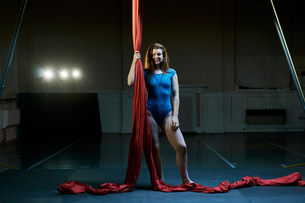 Portrait of young female aerial acrobat holding red silk ropeの写真素材 [FYI03568851]