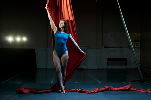 Young female aerial acrobat poised holding red silk ropeの写真素材 [FYI03568853]