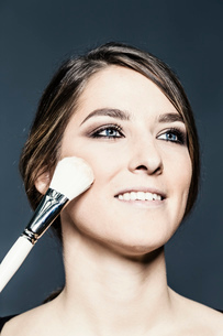 Blusher being applied to young woman's cheekの写真素材 [FYI03568894]