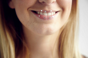 Cropped view of woman with glittery stars on lips smilingの写真素材 [FYI03568922]