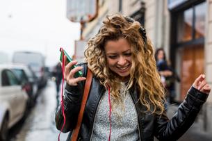 Woman in street listening to music through headphonesの写真素材 [FYI03568946]