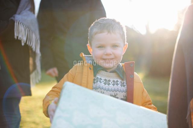 Happy boy carrying present with family in gardenの写真素材 [FYI03569114]