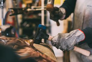 Hands of metalworker hammering copper in forge workshopの写真素材 [FYI03569154]