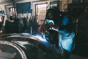 Metalworker in welding mask soldering metal in forge workshopの写真素材 [FYI03569173]