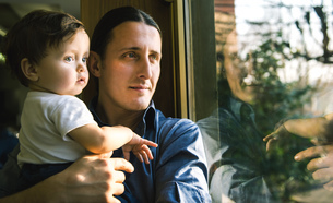 Mature man and baby son looking through windowの写真素材 [FYI03569197]