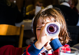 Portrait of boy looking through rolled paper in cafeの写真素材 [FYI03569204]
