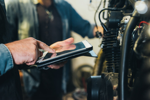Two mature men, working in garage, using digital tablet, close-upの写真素材 [FYI03569249]