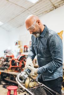 Mature man, working on motorcycle in garageの写真素材 [FYI03569250]