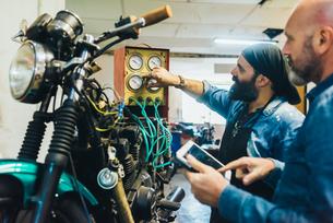 Two mature men, working on motorcycle in garageの写真素材 [FYI03569260]