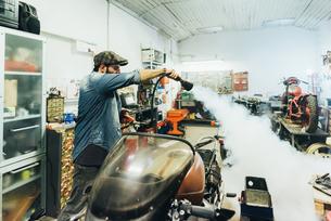 Mature man, working on motorcycle in garageの写真素材 [FYI03569269]