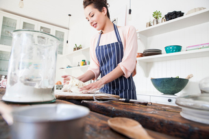 Young woman shaping dough at kitchen counterの写真素材 [FYI03569342]