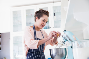 Young woman cracking egg into food mixer bowl at kitchen counterの写真素材 [FYI03569348]