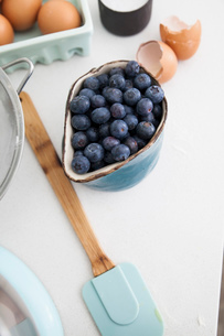 Cup of blueberries and carton of eggs on kitchen counterの写真素材 [FYI03569355]