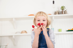 Portrait of cute girl with raspberries on her fingers in kitchenの写真素材 [FYI03569368]