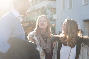Young man and female friends chatting in sunlit city streetの写真素材 [FYI03569398]