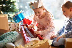 Girl and brother on living room floor gazing at toy guitar christmas giftの写真素材 [FYI03569469]
