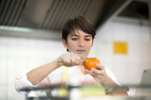 Young woman preparing food in fast food shopの写真素材 [FYI03569695]