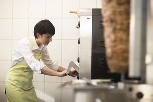Young woman cooking food in fast food shopの写真素材 [FYI03569701]