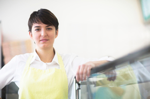 Portrait of young woman, working in fast food shopの写真素材 [FYI03569702]