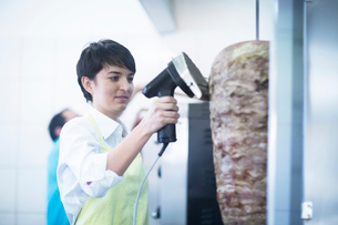 Young woman slicing kebab meat in fast food shopの写真素材 [FYI03569703]