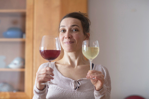 Woman holding up two glasses of red and white wineの写真素材 [FYI03569748]