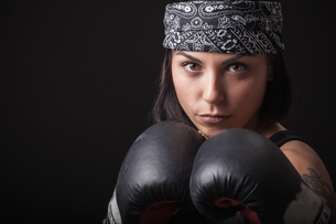 Portrait of young woman wearing boxing gloves, in fighting stanceの写真素材 [FYI03569860]