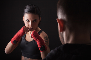 Portrait of young woman in fighting stance, facing fitness trainerの写真素材 [FYI03569862]