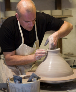 Male potter shaping clay pot on pottery wheel in workshopの写真素材 [FYI03569866]