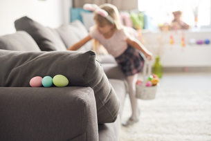 Girl searching for easter eggs on sofaの写真素材 [FYI03569892]