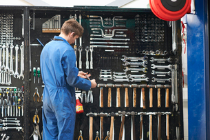 College mechanic student selecting wrench from repair garage tool kitの写真素材 [FYI03569917]