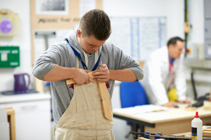 Male teenage carpentry student pushing wood joints together in college workshopの写真素材 [FYI03570094]