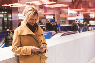 Woman looking at smartphone in underground stationの写真素材 [FYI03570131]