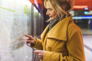 Woman pointing at street map in underground stationの写真素材 [FYI03570135]