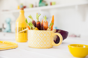 Cup of fresh colourful carrots on kitchen tableの写真素材 [FYI03570318]