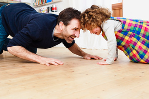 Mature man crawling head to head with daughter on kitchen floorの写真素材 [FYI03570341]
