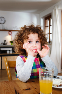 Girl sitting at table licking her thumbs after snackの写真素材 [FYI03570362]