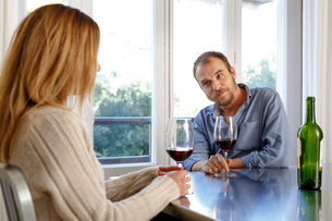 Mid adult couple at home, drinking glass of wine, having disagreementの写真素材 [FYI03570559]