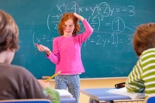 Primary schoolgirl scratching her head at equation on classroom blackboardの写真素材 [FYI03570678]