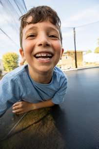 Portrait of young boy leaning on large trampoline, laughingの写真素材 [FYI03570844]