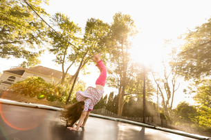 Young girl doing handstand on large trampoline, low angle viewの写真素材 [FYI03570846]
