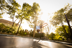 Young boy doing somersault on large trampoline, low angle viewの写真素材 [FYI03570848]