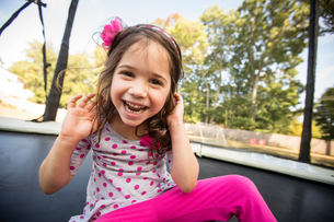 Portrait of young girl sitting on large trampoline, laughingの写真素材 [FYI03570849]