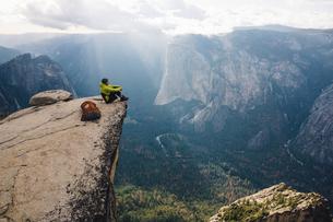Man sitting at top of mountain, overlooking Yosemite National Park, California, USAの写真素材 [FYI03570859]
