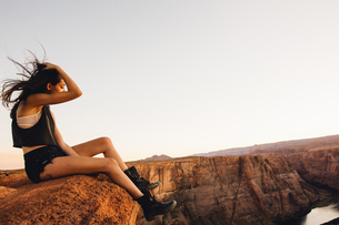 Woman relaxing and enjoying view, Horseshoe Bend, Page, Arizona, USAの写真素材 [FYI03570948]