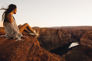 Woman relaxing and enjoying view, Horseshoe Bend, Page, Arizona, USAの写真素材 [FYI03570949]
