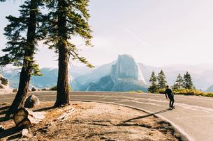 Skateboarder travelling on mountain road, Yosemite, California, USAの写真素材 [FYI03570979]